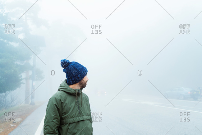 Full body side view of unrecognizable traveler in warm outerwear and hat walking on asphalt road leading through misty forest while hiking in Sierra de Madrid in Spain