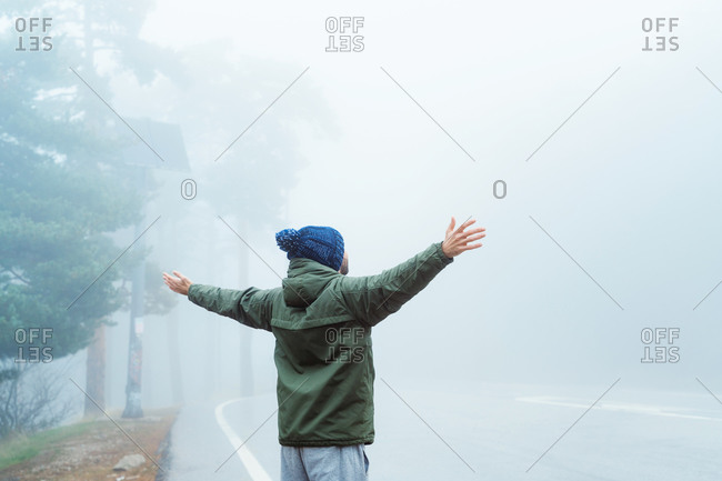 Full body back view of unrecognizable traveler in warm outerwear and hat walking on asphalt road leading through misty forest while hiking in Sierra de Madrid in Spain