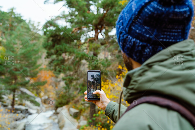 Side view of crop unrecognizable male backpacker in warm clothes with smartphone photographing river flowing in mountainous forest while travelling through Sierra de Madrid in autumn day
