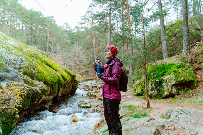 Side view of female adventurer in outerwear and with thermos standing near river with fast flow and enjoying nature during vacation in Sierra de Madrid