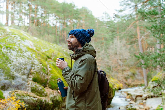 Side view of tranquil male traveler in warm clothes standing in woods and pouring aromatic hot tea in thermos mug during autumn vacation in Sierra de Madrid