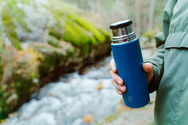 Closeup of crop unrecognizable tourist standing in nature with thermos cup filled with hot aromatic beverage during vacation in Sierra de Madrid
