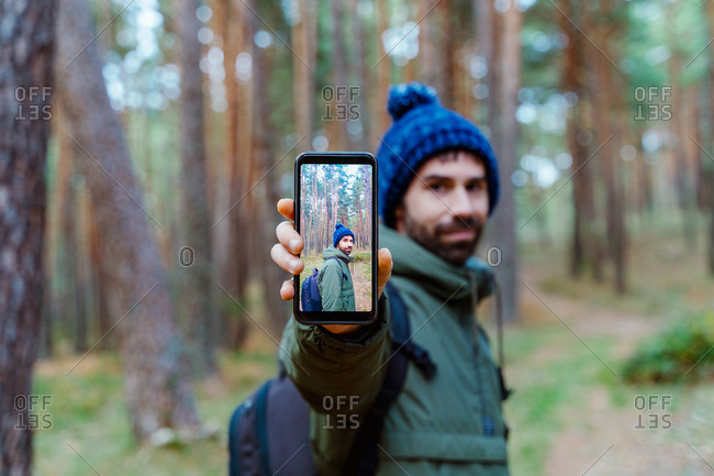 Side view of traveling man in warm outerwear standing in woods and showing smartphone with photo during autumn adventure in Sierra de Madrid