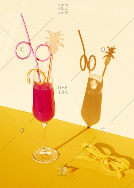 Pink cocktail with straw and orange peel in studio