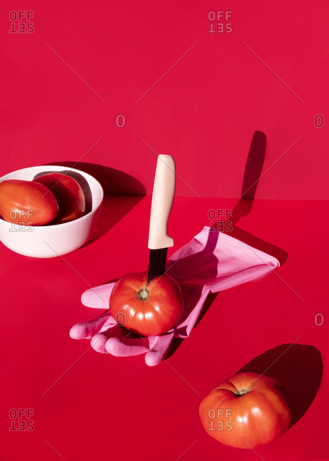 High angel of fresh tomato with sharp knife placed on rubber glove on red backwound in studio