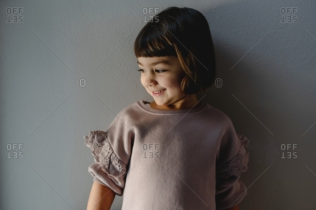 Cute little girl in casual outfit leaning on gray wall at home while smiling sincerely and looking away
