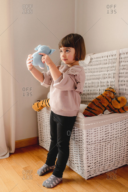 Adorable little girl standing near basket and playing with stuffed toy while entertaining at weekend at home