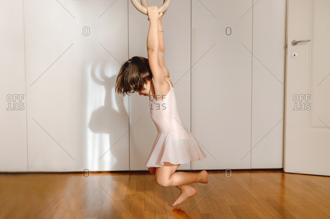 Adorable little girl in dress handing above floor on wooden gymnastic rings in bright room and looking away