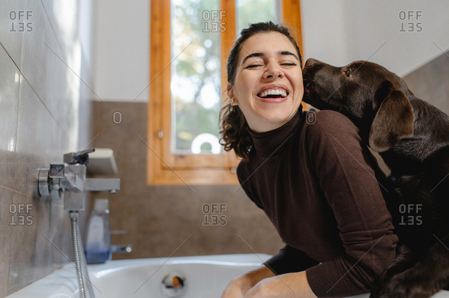 Side view of cheerful female owner and cute purebred Labrador puppy preparing for bath procedures in bathroom