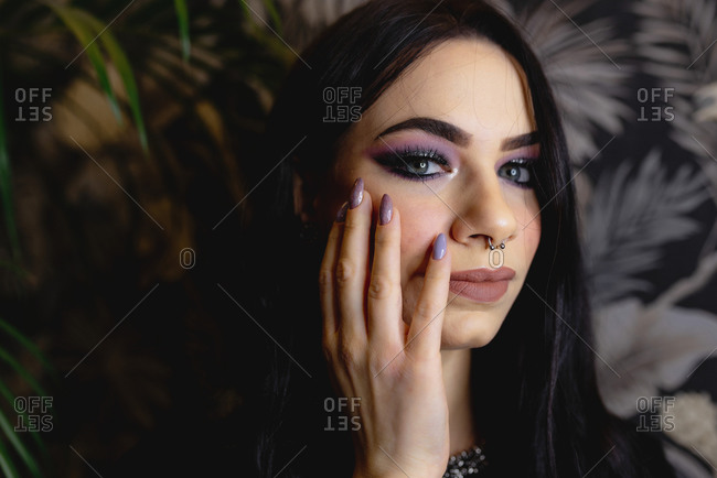 Positive young female with bright makeup and piercing covering eye and looking at camera while standing near wall with floral ornament