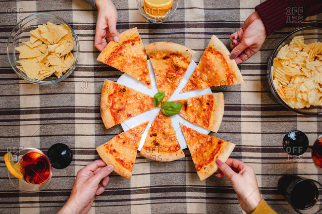 Top view of crop unrecognizable friends gathering at table and eating delicious pizza at home while enjoying weekend together