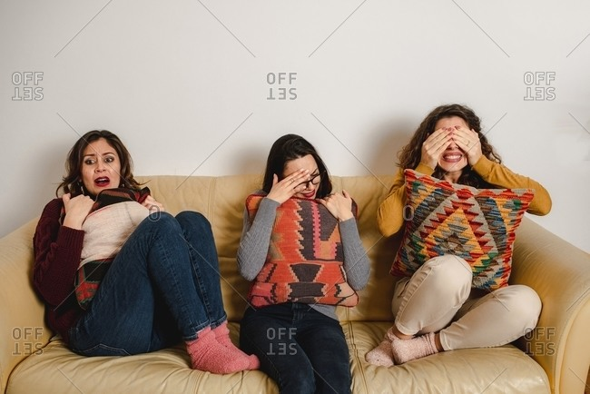 Group of frightened female friends sitting on sofa at home and watching horror movie together while covering eyes and feeling fear