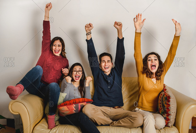 Group of excited friends watching football match and celebrating victory with raised arms while shouting and looking forward