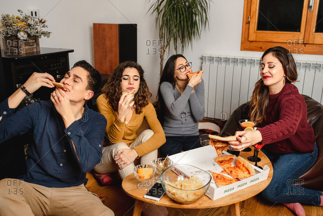 Group of content friendly people gathering at home and enjoying delicious takeaway pizza at weekend