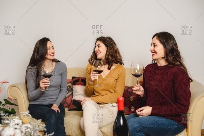 Group of friendly females sitting on sofa at home and drinking red wine while enjoying meeting at weekend and talking to each other