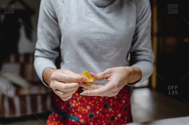 Crop anonymous female standing with traditional Italian tortellini in kitchen at home