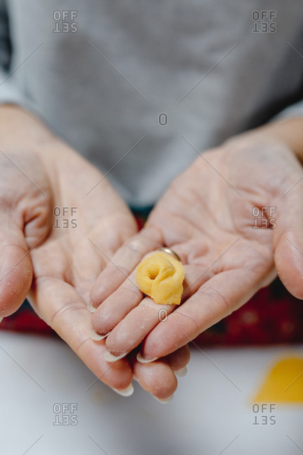 High angle of crop anonymous female standing with traditional Italian tortellini in kitchen at home