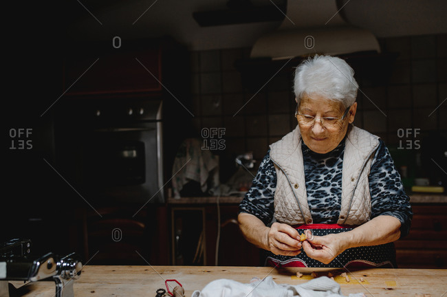 Aged housewife preparing delicious homemade tortellini while standing at table in kitchen at home