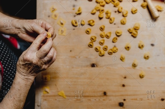 From above of crop unrecognizable senior female cooking tasty traditional tortellini at wooden table in cozy kitchen