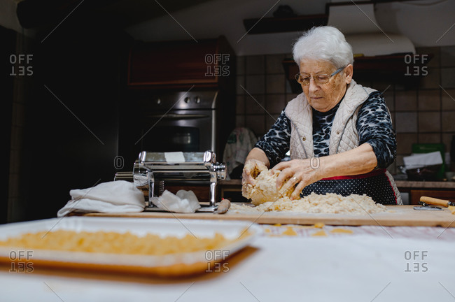 Senior female standing at table in cozy kitchen and kneading raw dough while preparing pastry for cooking domestic Italian tortellini
