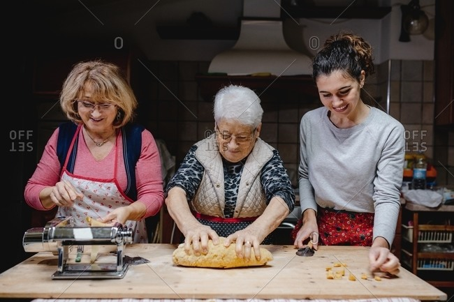 Content relative women standing at table in kitchen and preparing delicious traditional Italian tortellini together
