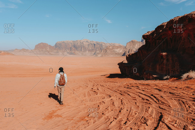 Back view of unrecognizable explorer in outerwear standing on sandy ground of Wadi Rum sandstone valley on sunny day and admiring amazing scenery during vacation in Jordan
