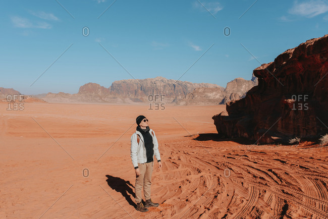 Explorer in outerwear standing on sandy ground of Wadi Rum sandstone valley on sunny day and admiring amazing scenery during vacation in Jordan