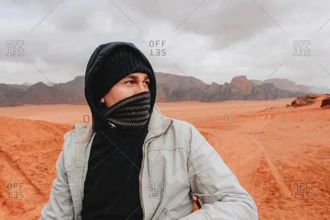 Explorer in outerwear with scarf around mouth standing on sandy ground of Wadi Rum sandstone valley on sunny day and admiring amazing scenery during vacation in Jordan