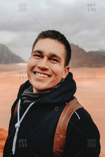 Delighted male tourist with backpack standing in Wadi Rum valley and looking at camera while enjoying holiday in Jordan