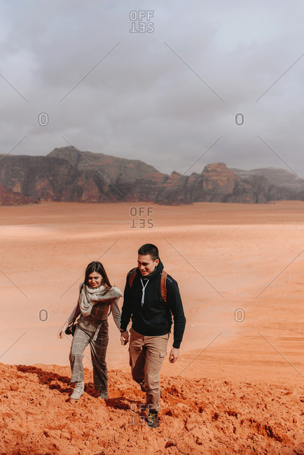 Couple of travelers running down sandy hill in Wadi Rum sandstone valley while enjoying freedom and vacation in Jordan looking away
