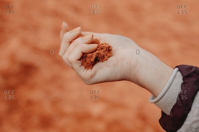 Unrecognizable crop person with handful of red sand standing in Wadi Rum dry valley in Jordan