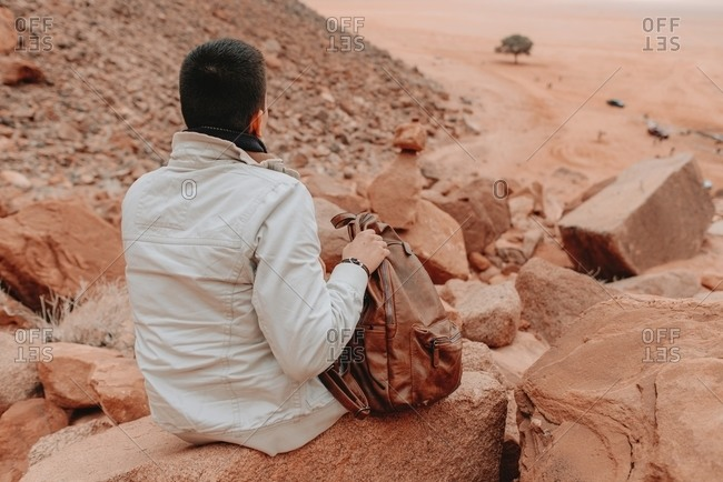Back view of traveling man relaxing on rock in Wadi Rum valley and enjoying amazing scenery during vacation