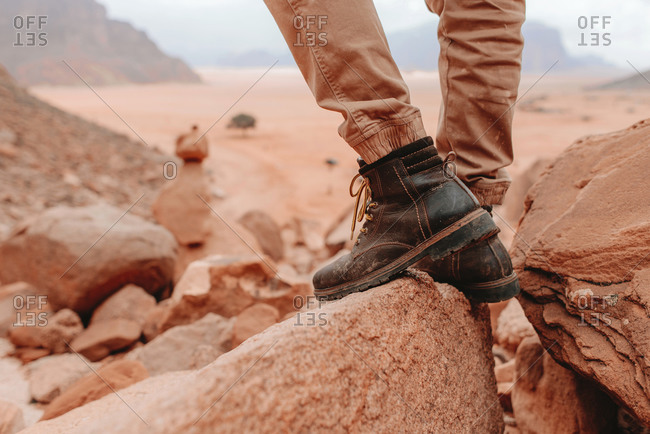 Legs of crop male tourist in hiking boots standing on rocks in Wadi Rum sandstone valley during holiday in Jordan