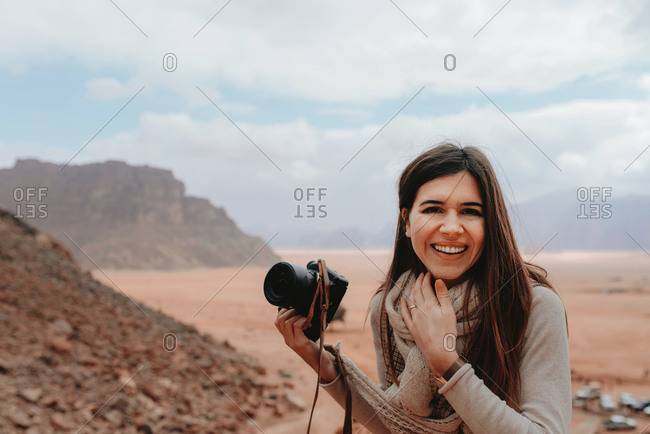 Delighted traveling female photographer with professional camera standing in desert in Wadi Rum and looking at camera while enjoying vacation