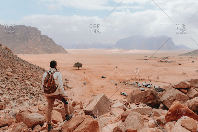Back view of unrecognizable peaceful male tourist with photo camera standing in Wadi Rum on background of camp with cars looking away while observing scenic view