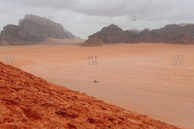 Scenic view of automobile riding in sandstone valley in Wadi Rum on cloudy day
