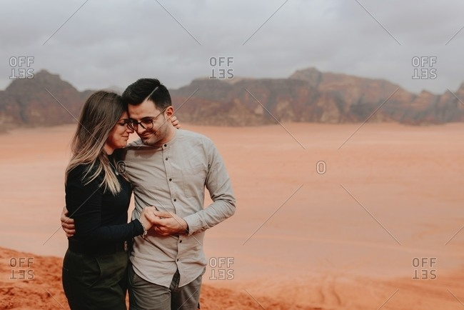 Smiling traveling couple tenderly embracing while standing in Wadi Rum on background of sandstone valley with rocks