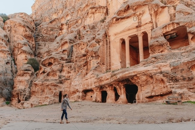 Side view of female tourist walking near ancient The Treasury temple during vacation in Petra