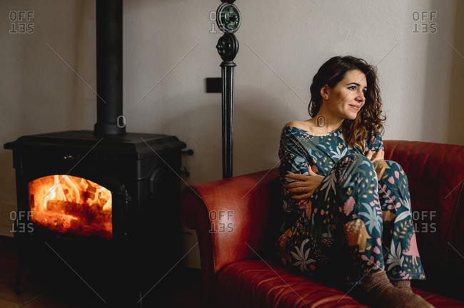 Attractive caucasian woman portrait sitting on the sofa. Girl wearing sleepwear next to the fireplace in the living room with a guitar. Cozy, comfortable, winter, domestic life concept.