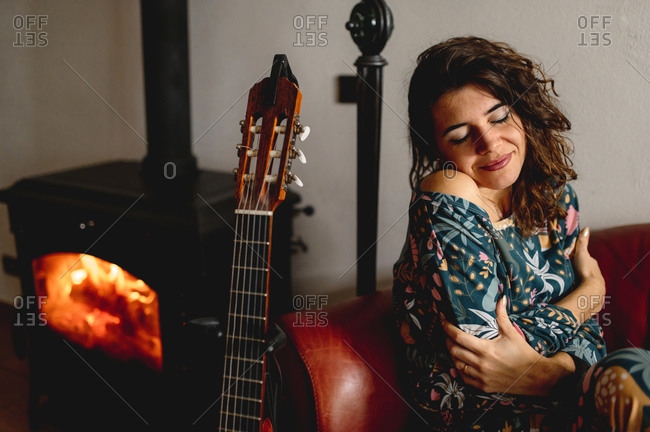 Close-up portrait of sensual attractive caucasian woman sitting on the sofa. Girl wearing sleepwear next to the fireplace with guitar in the living room. Cozy, winter, life at home concept.