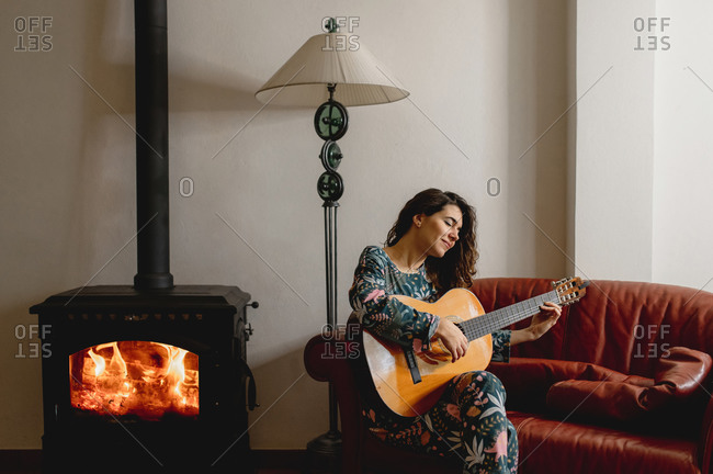 Young caucasian sensual woman portrait wearing sleepwear sitting on the sofa in her living room next to a fireplace. Girl playing guitar. Leisure, domestic life, cozy concept.