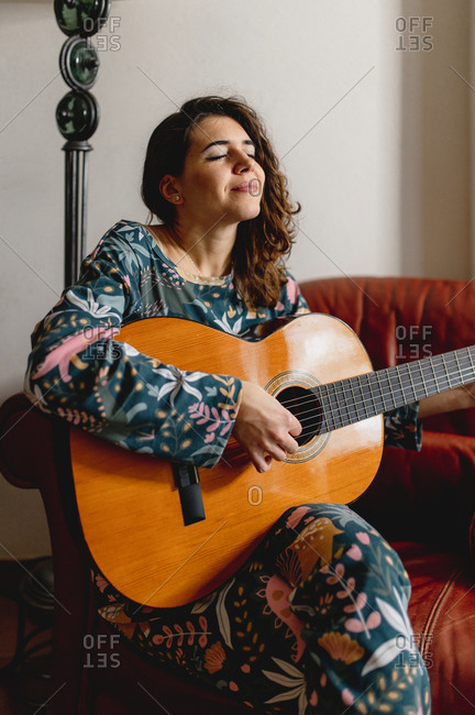 Vertical young caucasian sensual woman portrait wearing sleepwear sitting on the sofa. Girl playing guitar, practicing and enjoying the music. Leisure, domestic life, cozy concept.