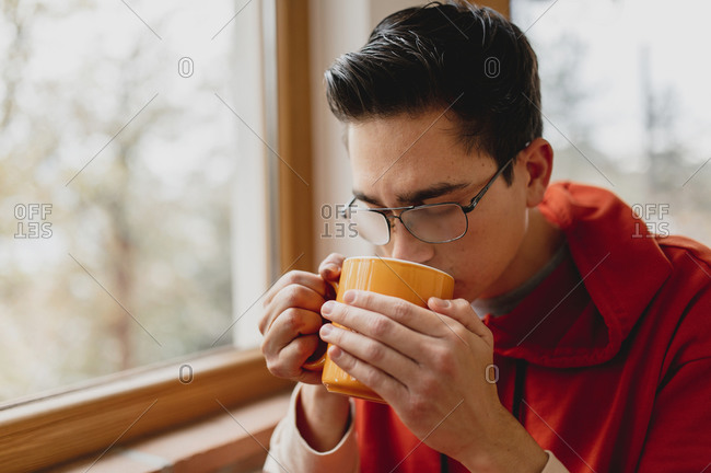 Close-up young caucasian man portrait sitting on the bed next to a glass window drinking a cup of hot tea or coffee. Winter, domestic life, comfort concept.