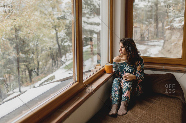 Close up caucasian attractive woman portrait smiling while drinking a cup of hot beverage.