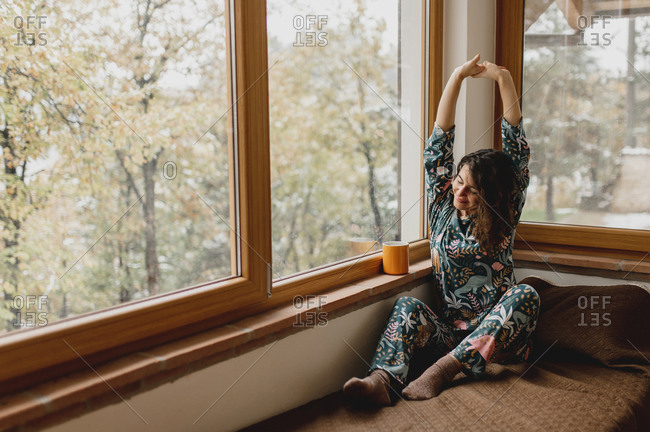 Close up caucasian attractive woman portrait waking up and stretching. Lady sitting on the bed in a beautiful full of glass windows bedroom with cup of tea or coffee.