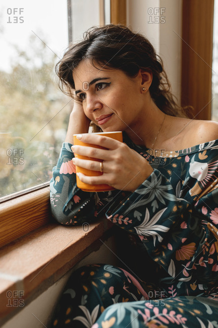 Close up caucasian attractive woman portrait smiling while drinking a cup of hot beverage. Girl sitting on the bed in a beautiful bedroom full of glass windows looking outside the snowy landscape.