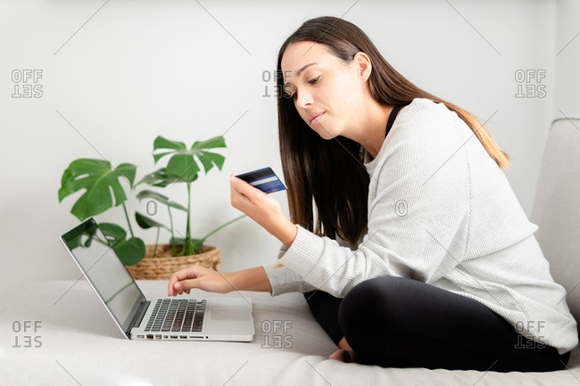 Female buyer sitting on sofa at home and making payment with plastic card while shopping online via laptop