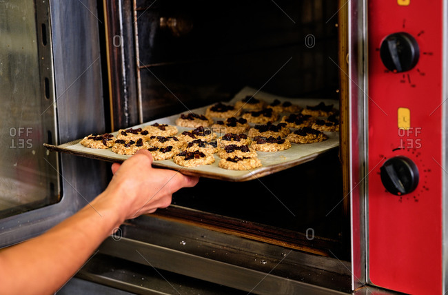 Crop anonymous baker putting baking sheet with sweet cookies with fruits into hot oven while working in industrial kitchen