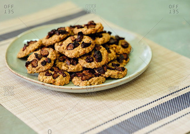 Freshly baked short crust cookies with dried fruits on plate in kitchen