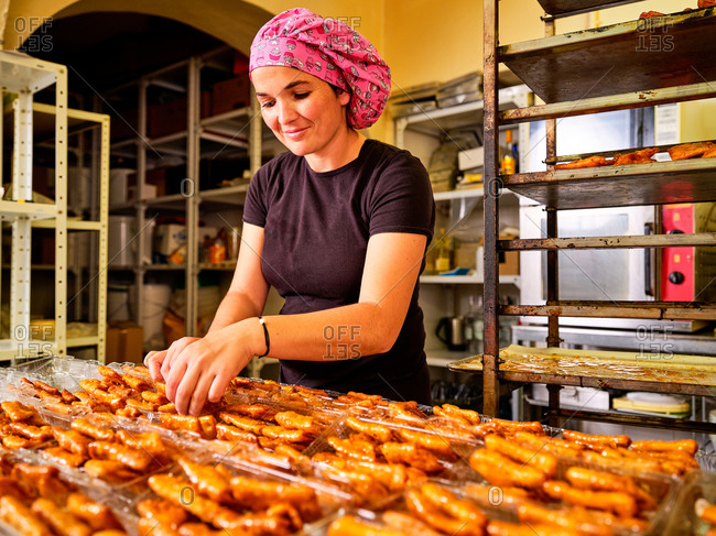 Professional female baker arranging fresh pastry in plastic containers for selling while working in bakery